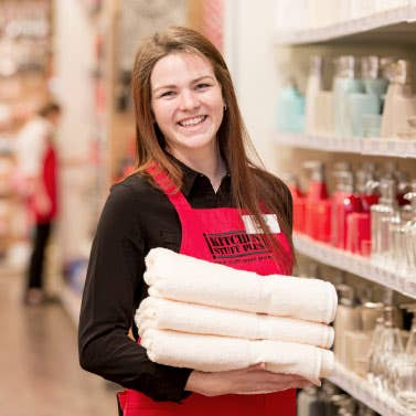 Sales Associate in red apron, holding 3 stacked towels