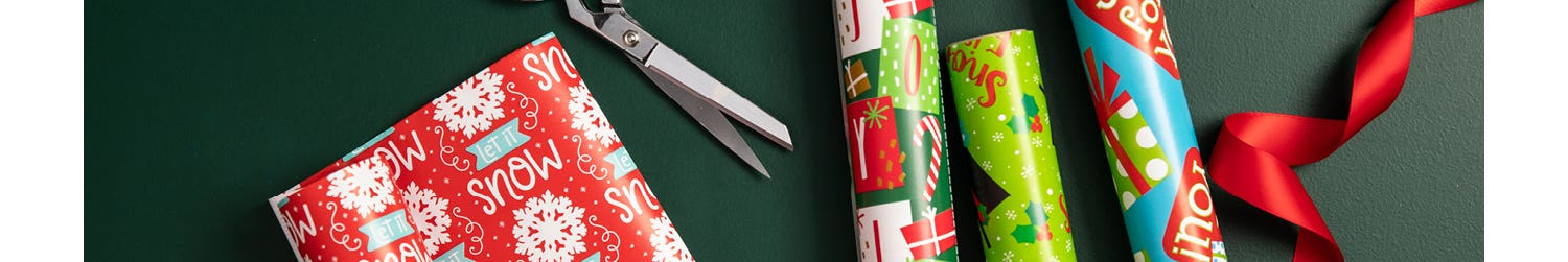 coulourful festive wrapping paper, red silk ribbon, and scissors on a dark green background
