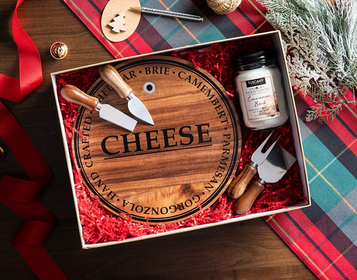 cheese board and scented candle in a gift box, on a plaid tablecloth on a wooden table, and evergreen branches