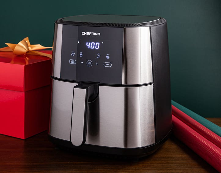 Air fryer and red present with yellow bow on a wooden table top with a dark green background.