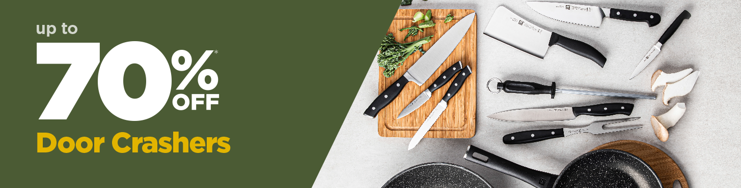 several knives on a cutting board, and pans with some mushrooms and broccoli