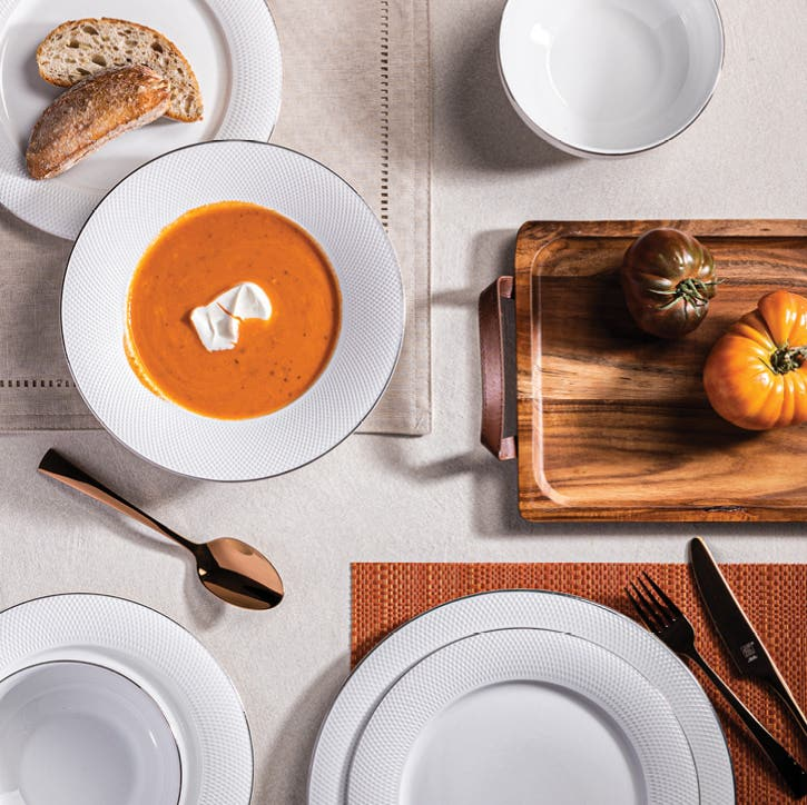 pot of soup on the table with a bowl of soup, cutting board with sliced baguette on a placemat