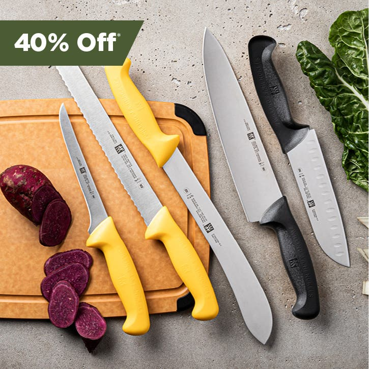 Black and yellow handle knives, 3 on a cutting board, 2 on the countertop