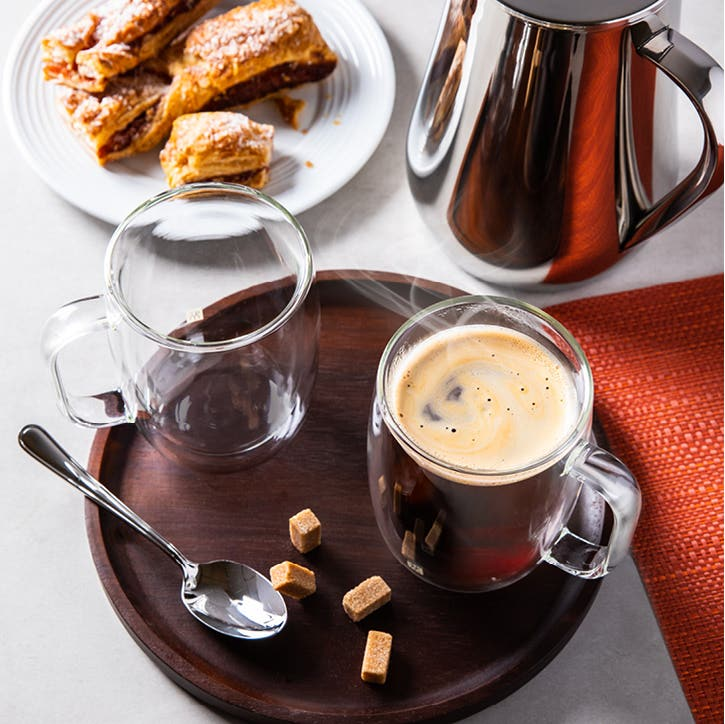 2 double wall coffee mugs, a small spoon, and brown sugar cubes on a wooden tray, and a plate with pastries