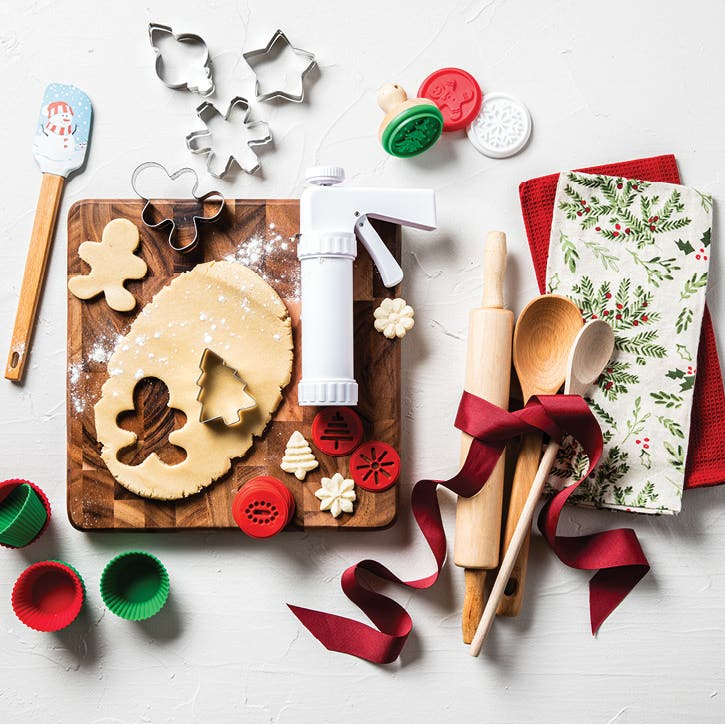 silicone muffin tin liners, wooden spoons and spatulas, cookie press and cookie cutters on a cutting board with cookie dough