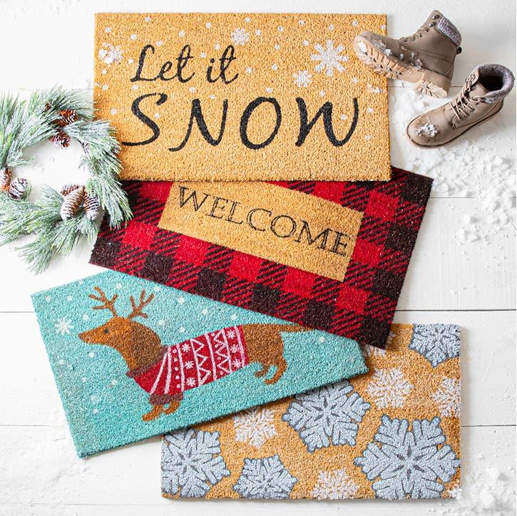 4 Christmas-themed coir mats on a front step